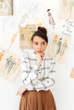 Serious thinking woman fashion illustrator. Image of young serious thinking woman fashion illustrator standing near a lot of illustrations. Looking aside Royalty Free Stock Photos