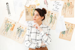 Serious thinking woman fashion illustrator. Image of young serious thinking woman fashion illustrator standing near a lot of illustrations. Looking aside royalty free stock photography