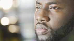 Serious thoughtful African American man looking into future, face close-up