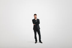 Serious thoughtful businessman in formal wear. Holding his hand at chin and looking down over light grey background royalty free stock photo