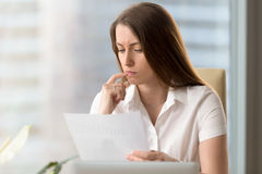 Serious thoughtful businesswoman analyzing financial document, s royalty free stock images