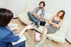 Serious and thoughtful couple is sitting together on sofa with hands crossed. They are looking at therapist. Doctor is. Looking and talking to this couple Stock Photography