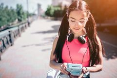 Serious and thoughtful girl is standing outside on street and looking on her music player. She wears glasses. Also there royalty free stock photography