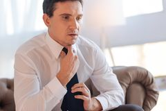 Serious thoughtful man getting ready for an unpleasant conversation. Preparation. Thoughtful unhappy nervous man sitting in an armchair and knotting a tie while Stock Photography