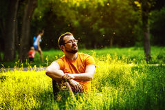 A serious thoughtful man is sitting on green grass in a park Stock Images