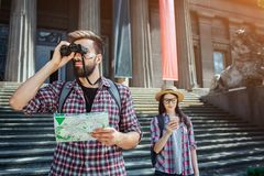 Serious and thoughtful man stand outside and look in binoculars. Also he holds map in hand. Female traveller stand royalty free stock photos