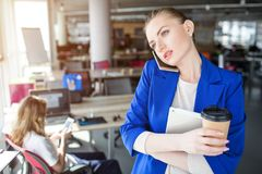 Serious and thoughtful person is talking on the phone. She holds a cup of coffee and a notebook. Girl is looking to the royalty free stock photo