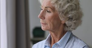 Serious thoughtful senior woman looking through window at home stock footage