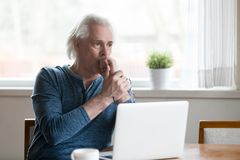 Serious thoughtful senior man looking away thinking of problem s. Serious thoughtful mature senior man looking away thinking of online problem solution near royalty free stock photos