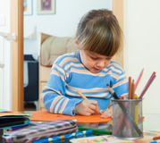 Serious three year old  drawing on paper Stock Photos