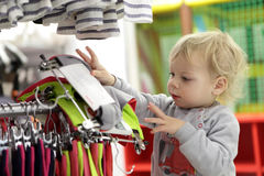 Serious toddler choosing clothes. In a market royalty free stock image