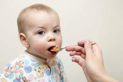Serious toddler has dinner Stock Photos