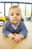 Serious Toddler Lying on the Floor Stock Image