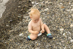 Serious toddler sits on stone beach and looking at sunset Stock Images