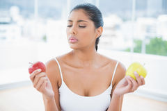 Serious toned brunette holding apples Stock Photo