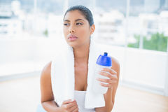 Serious toned brunette with towel holding sports bottle Royalty Free Stock Image