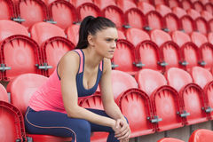 Serious toned young woman sitting on chair in the stadium Royalty Free Stock Photos