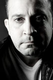Serious Tough Guy. Portrait of a serious middle aged man in black in white royalty free stock images