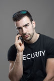 Serious tough security agent talking on the phone looking at camera. Royalty Free Stock Images