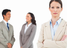 Serious tradeswoman with talking colleagues behind her Royalty Free Stock Photos