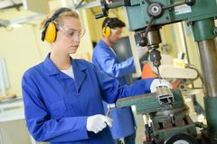 Serious trainees focused on drilling metal piece with professional machinery stock images
