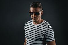 Serious trendy man in striped t-shirt and sunglasses looking at camera. Isolated on grey royalty free stock photography