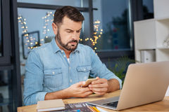Serious troubled man checking his messages. This is important. Serious nice troubled man holding a smartphone and checking his messages while sitting in front of stock image