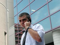 Serious troubles. Businessman discussing on the phone in front of a corporate building Royalty Free Stock Photos