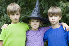 Serious twins and girl in carnival hat stock photos