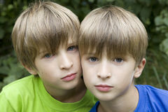 Serious twins hugging in park royalty free stock photo