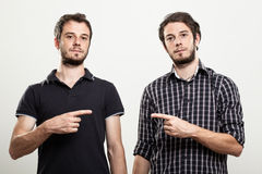 Serious Twins Pointing Each Other stock photography