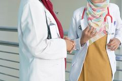 Serious two female asian hijab doctor discuss and studying about patient`s document on the hospital room stock photography