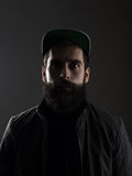 Serious unconventional bearded man wearing baseball cap staring at camera. High contrast low key dark shadow portrait over black background Stock Images