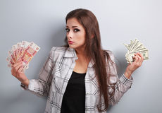 Serious unhappy business woman thinking that currency to choose, Royalty Free Stock Photography