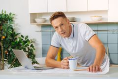 Serious unhappy man holding cup of tea. Tired from work. Serious unhappy adult man holding a cup of tea and feeling tired while working on a project Royalty Free Stock Photos