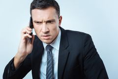 Serious unhappy man listening to his interlocutor. Bad news. Serious unhappy smart businessman listening to his interlocutor and showing his emotions while Royalty Free Stock Photography