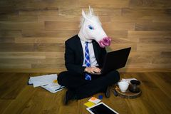 Serious unicorn in a suit and tie works at home office with gadgets. Young man in funny rubber mask sits on the floor against a wall and works with laptop Royalty Free Stock Photo