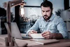 Serious unshaken man sitting and focusing on the letter. Important note. Serious unshaken busy man sitting in the cabinet by the table using the laptop and Stock Images