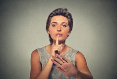 Serious upset woman finger, hand on lips, shhh gesture asking be quiet silence. Closeup portrait serious upset woman finger, hand on lips, shhh gesture asking be Royalty Free Stock Photography