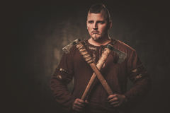 Serious viking with axes in a traditional warrior clothes, posing on a dark background. Royalty Free Stock Images