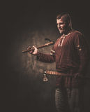 Serious viking with axes in a traditional warrior clothes, posing on a dark background. Stock Photo