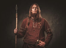 Serious viking with a spear in a traditional warrior clothes, posing on a dark background. Stock Photography