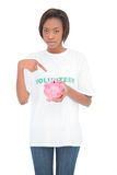 Serious volunteer woman pointing at her piggy bank Royalty Free Stock Photos