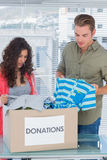 Serious volunteers taking out clothes from a donation box Stock Images