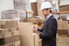 Serious warehouse manager checking inventory Royalty Free Stock Photos