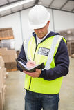 Serious warehouse worker with diary Stock Images