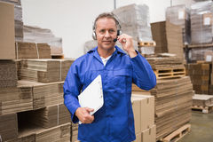 Serious warehouse worker using headset. In warehouse Royalty Free Stock Photos