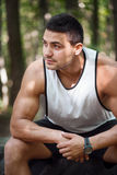 Serious well built man sitting in the park Royalty Free Stock Photography