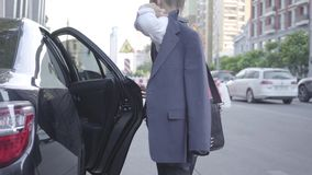 Serious well-dressed boy getting out of the car and walking down the street. Urban cityscape in the background. Young stock footage