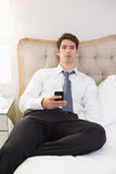 Serious well dressed man with cellphone sitting in bed Royalty Free Stock Images